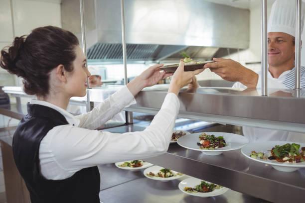 waiter in kitchen with chef