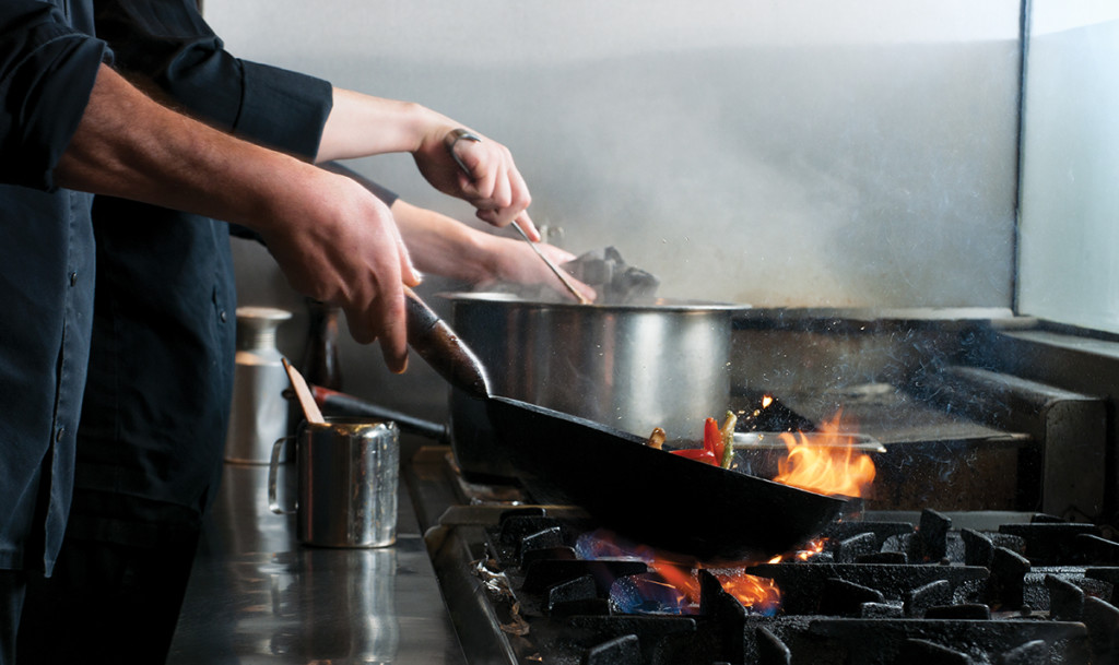 chef flambe vegetables in frying pan on stove in commercial kitchen